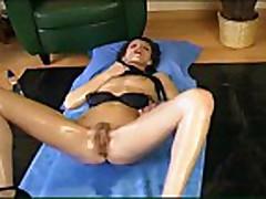 Oiled brunette masturbating and fisting both ways